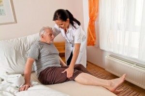 nurse helps an elderly patient into bed
