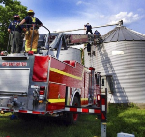Firemen try to save farmer in grain bin