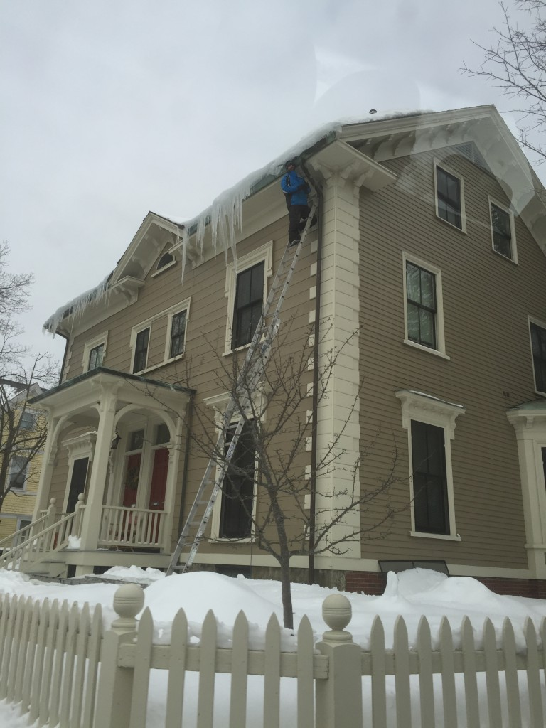 This man is putting himslef in a precarious situation trying to knock off icicles from a house.